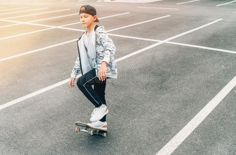 Teenager skateboarder boy with a skateboard on asphalt playground doing tricks. Youth generation Freetime spending concept image royalty free stock photo