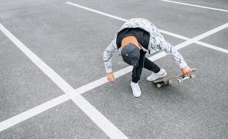 Teenager skateboarder boy with a skateboard on asphalt playground doing tricks. Youth generation Freetime spending concept image stock photography