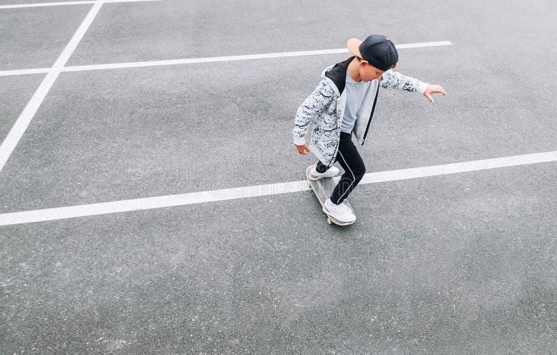 Teenager skateboarder boy with a skateboard on asphalt playground doing tricks. Youth generation Freetime spending concept image stock images