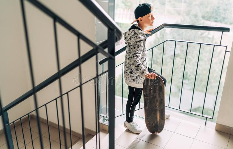 Teenager skateboarder boy with a skateboard going up by staircase home. Youth generation Freetime spending concept image stock photo