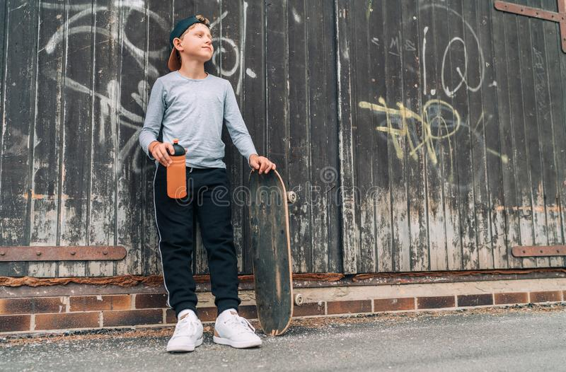 Teenager skateboarder boy standing beside a wooden grunge graffiti wall with skateboard and Water bottle flask. Youth generation royalty free stock image