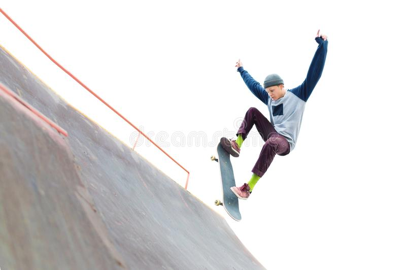 The teenager skateboarder in the cap does a trick with a jump on the ramp in the skatepark. Isolated skater and ramp on stock photography