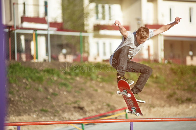 A teenager skateboarder does an ollie trick in a skatepark on the outskirts of the city. Against the background of the sleeping area royalty free stock photography