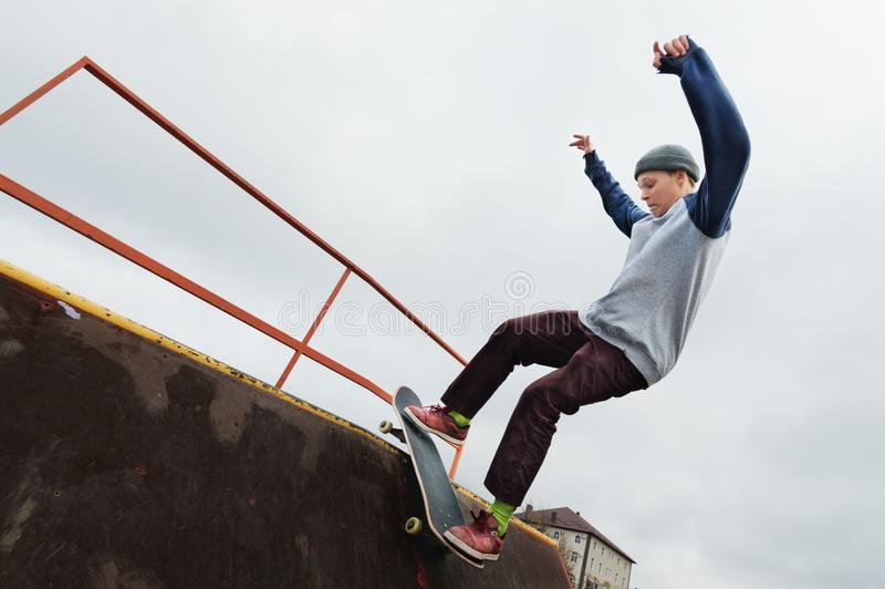 A teenager skateboarder in a hat does a Rocks trick on a ramp in a skate park against a cloudy sky and sleeping area royalty free stock image