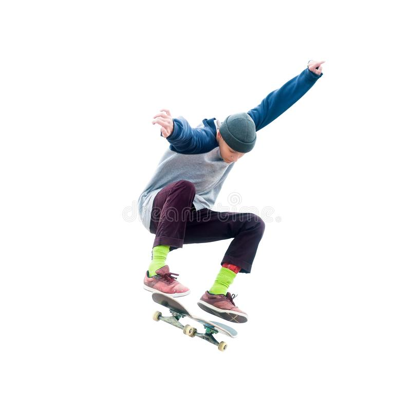 Teenager skateboarder jumps ollie on an isolated white background. The concept of street sports and urban culture royalty free stock image