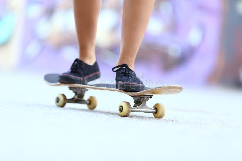 Teenager skater girl legs on a skate board royalty free stock image