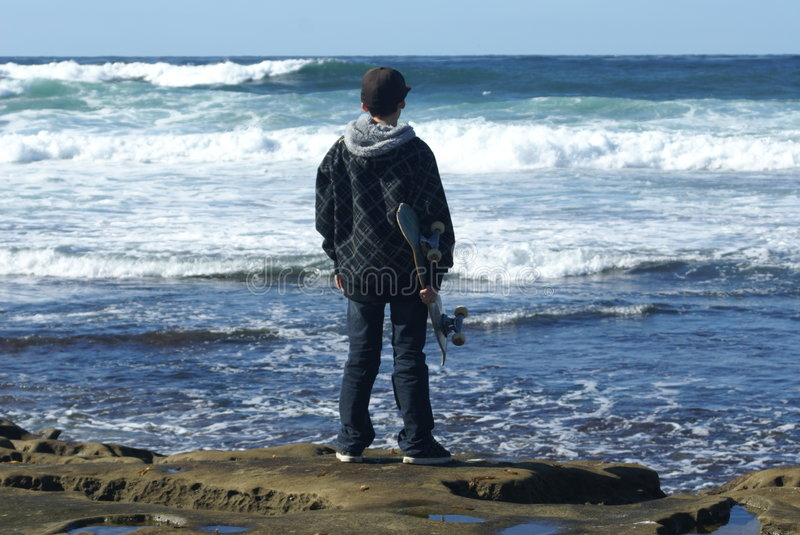 Teenager with skaterboard watching waves stock photography