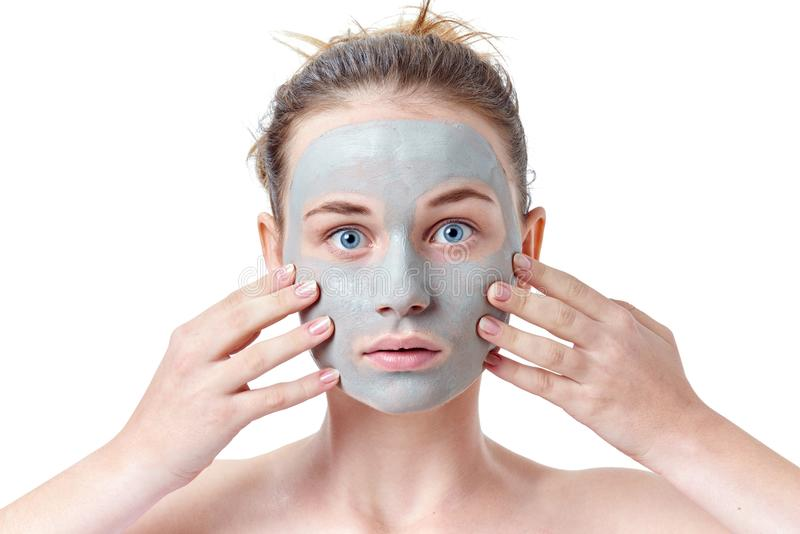 Teenager skincare concept. Young teen girl with dried clay facial mask making funny face, isolated on white stock photos