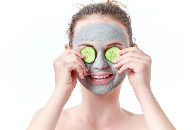Teenager skincare concept. Young teen girl with dry clay facial mask covering her eyes with two slices of cucumber smiling. Isolated on white background royalty free stock images