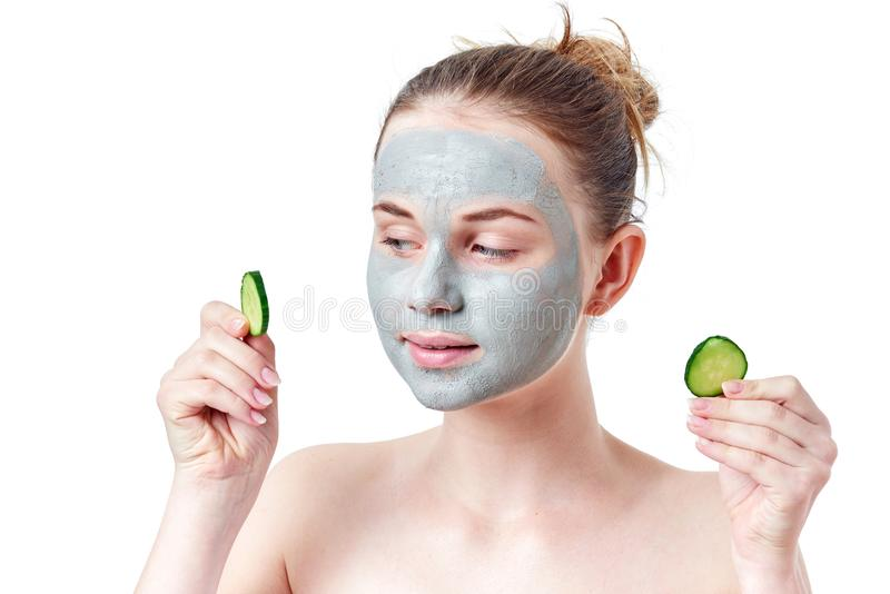 Teenager skincare concept. Young teen girl with dry clay facial mask holding two slices of cucumber. Isolated on white background stock images