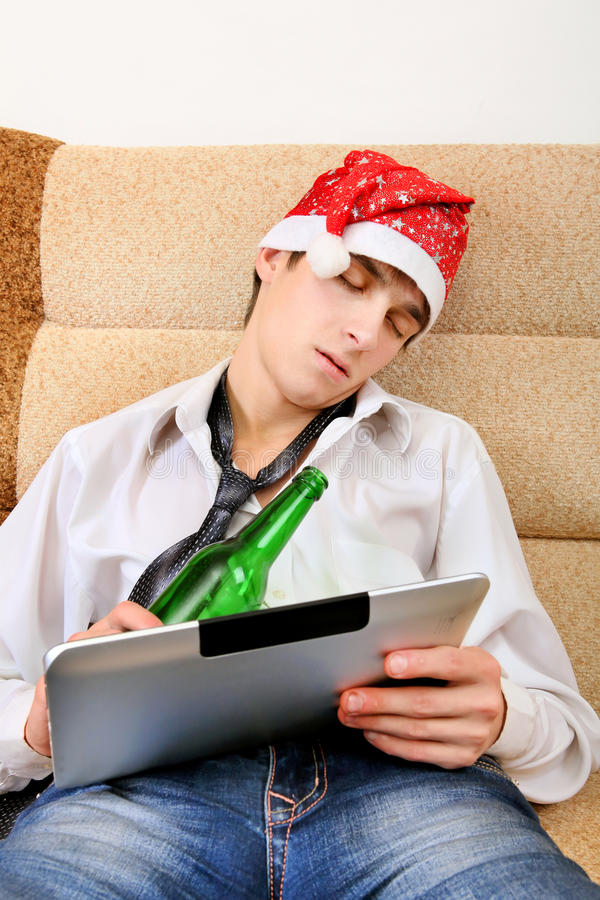 Teenager sleeping with a Beer and Tablet stock photo