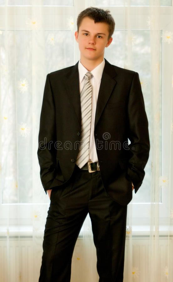 Teenager in smart black suit. Portrait of handsome young teenage boy, with thoughtful expression, in smart black suit with belt and white shirt and striped tie royalty free stock photography
