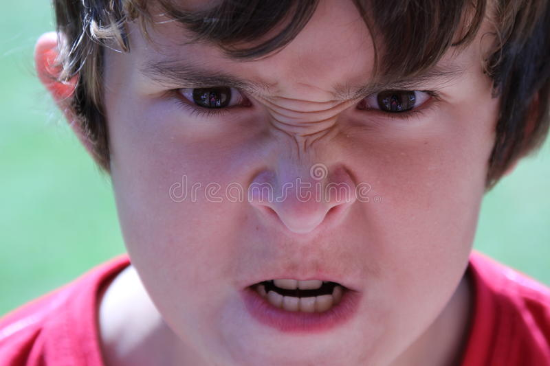 Teenager snarling. Adolescent angry boy, growling at the camera royalty free stock photography