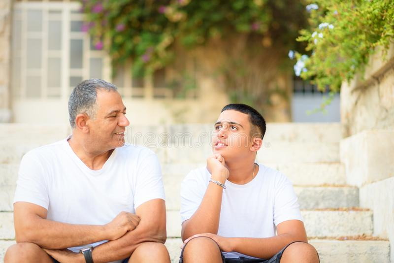 Happy teen young boy rest on stairs speak with elderly father enjoy leisure family weekend. royalty free stock images