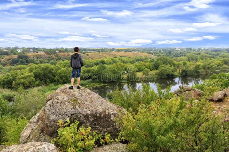 A teenager stands on top of a large stone boulder on the banks of the Southern Bug and looks into the distance. A teenager stands on top of a large stone boulder royalty free stock images