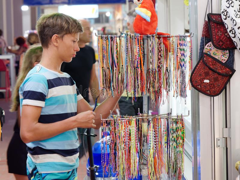 A teenager in a store chooses a souvenir royalty free stock photography