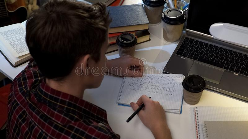 Teenager student drinking much coffee, writing in notebook, preparation for exam royalty free stock image