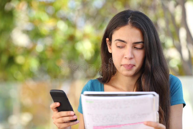 Teenager student girl looking sideways at mobile phone while studying. In a park with a green background stock image