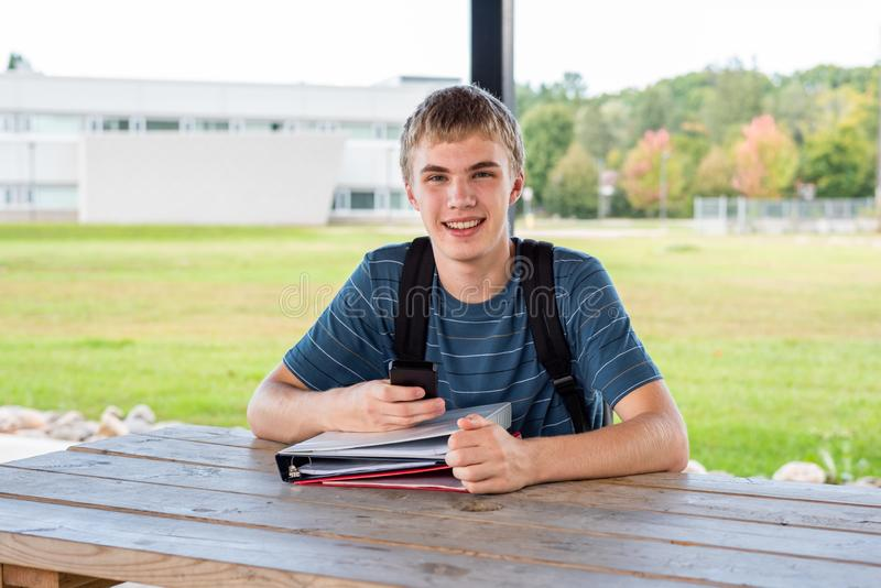 Teenager studying outdoors in a park. stock image