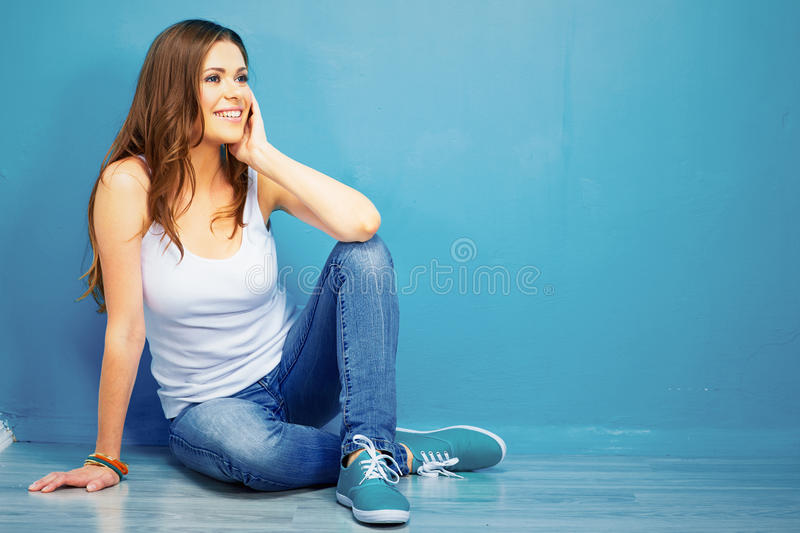 Teenager stylish model full body portrait sitting on floor. Smiling young woman royalty free stock photography