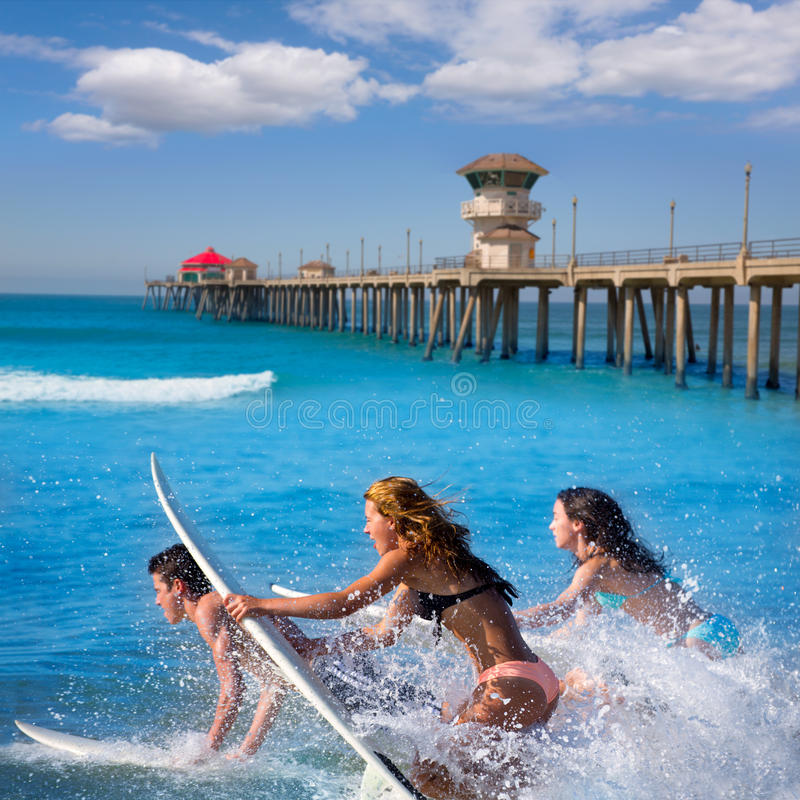 Teenager surfers running jumping on surfboards. Teenager surfers surfing running jumping on surfboards at Huntington beach pier California royalty free stock photography