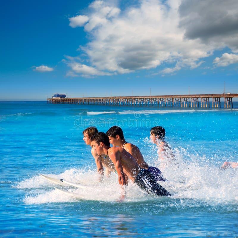 Teenager surfers running jumping on surfboards. Teenager surfers surfing running jumping on surfboards at Newport pier beach California stock photo