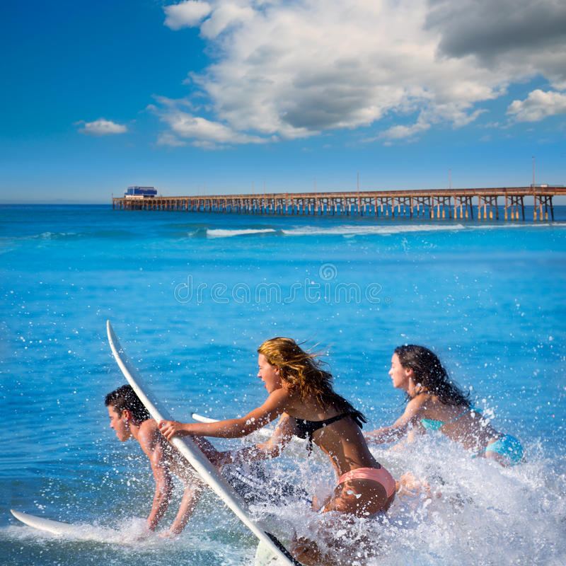 Teenager surfers running jumping on surfboards. Teenager surfers surfing running jumping on surfboards at Newport pier beach California royalty free stock image