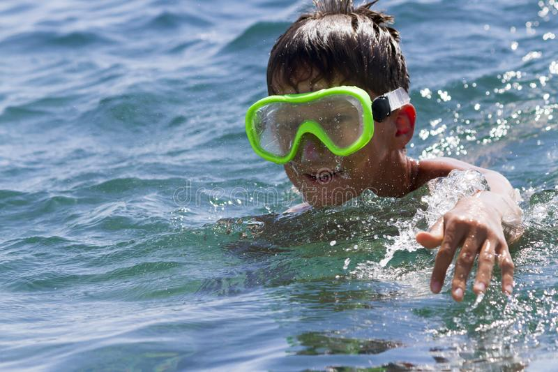 The teenager swims in a mask in the blue sea in clear day. The teenager swims in a mask in the blue sea in clear summer day stock photos