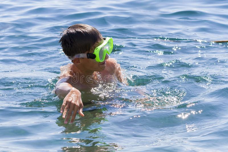 The teenager swims in a mask in the blue sea in clearday. The teenager swims in a mask in the blue sea in clear summer day stock photos