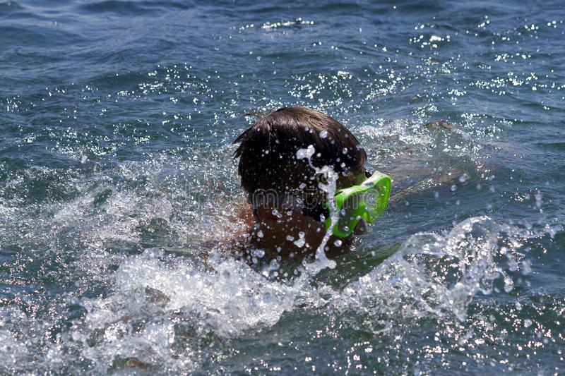 The teenager swims in a mask in the blue sea in clearday. The teenager swims in a mask in the blue sea in clear summer day stock images