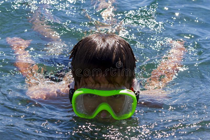 The teenager swims in a mask in the blue sea in clearday. The teenager swims in a mask in the blue sea in clear summer day royalty free stock photos