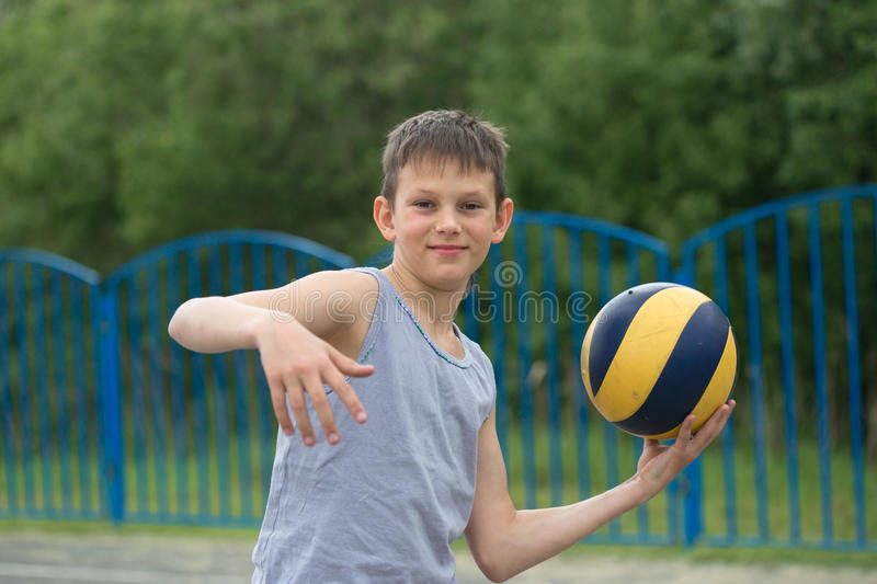Teenager in a T-shirt and shorts playing with a ball royalty free stock photography