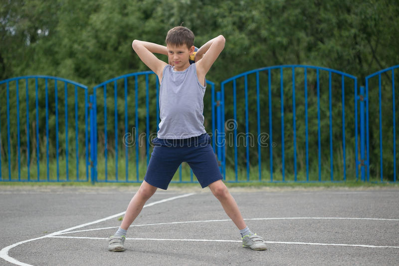 Teenager in a T-shirt and shorts playing with a ball royalty free stock photo