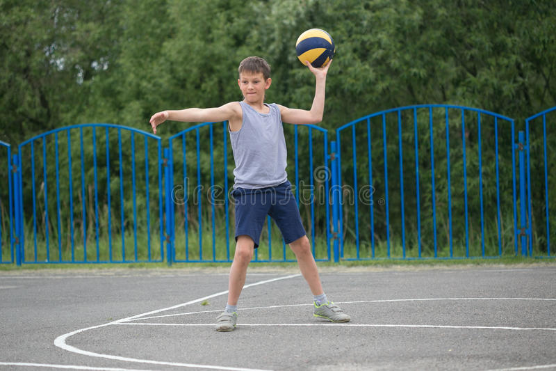 Teenager in a T-shirt and shorts playing with a ball stock photos
