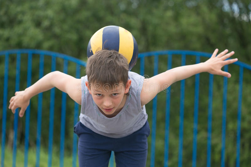 Teenager in a T-shirt and shorts playing with a ball royalty free stock photos