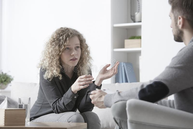 Teenager talking about interpersonal relationships. Teenager talking to a counselor about her interpersonal relationships in the office royalty free stock photo