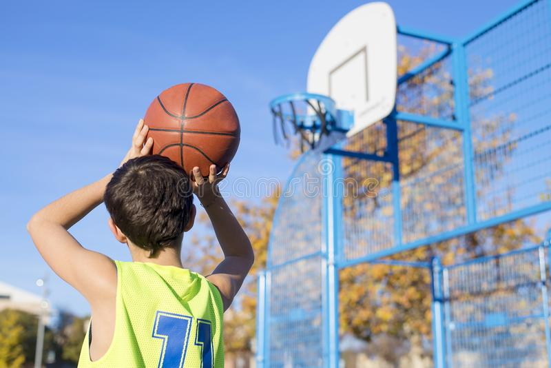 Teenager throwing a basketball into the hoop from behind. Teenager throwing a basketball into the hoop royalty free stock images