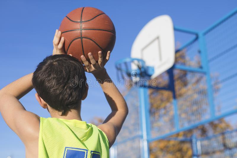 Teenager throwing a basketball into the hoop. From behind royalty free stock image