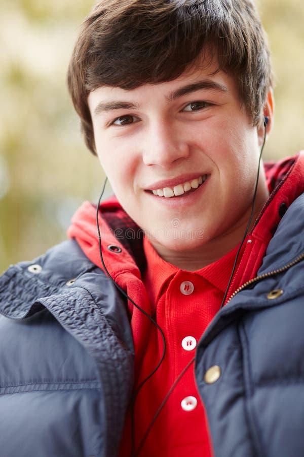 Teenager-tragende Kopfhörer, die Musik hören stockbild