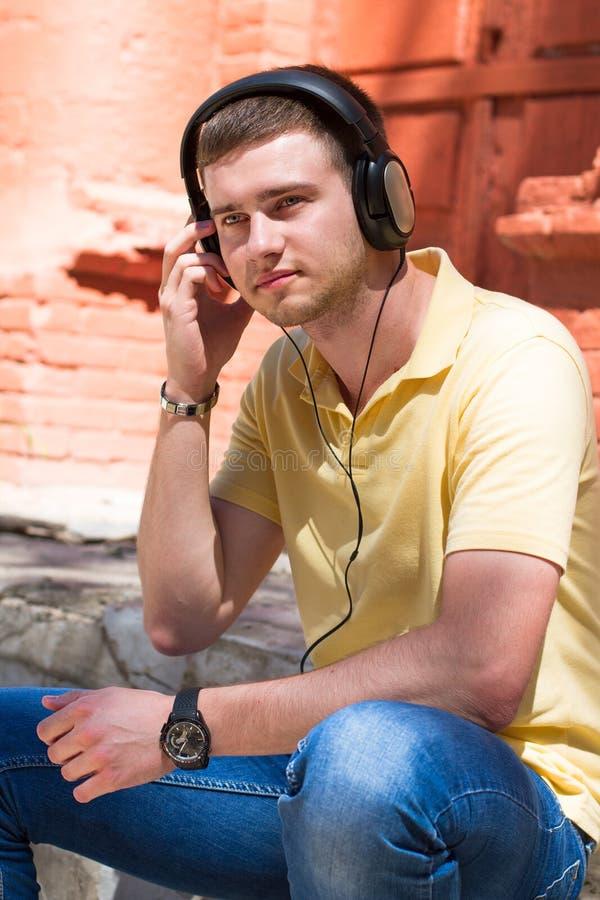 Teenager-tragende Kopfhörer und Hören Musik in städtischem stockfotografie