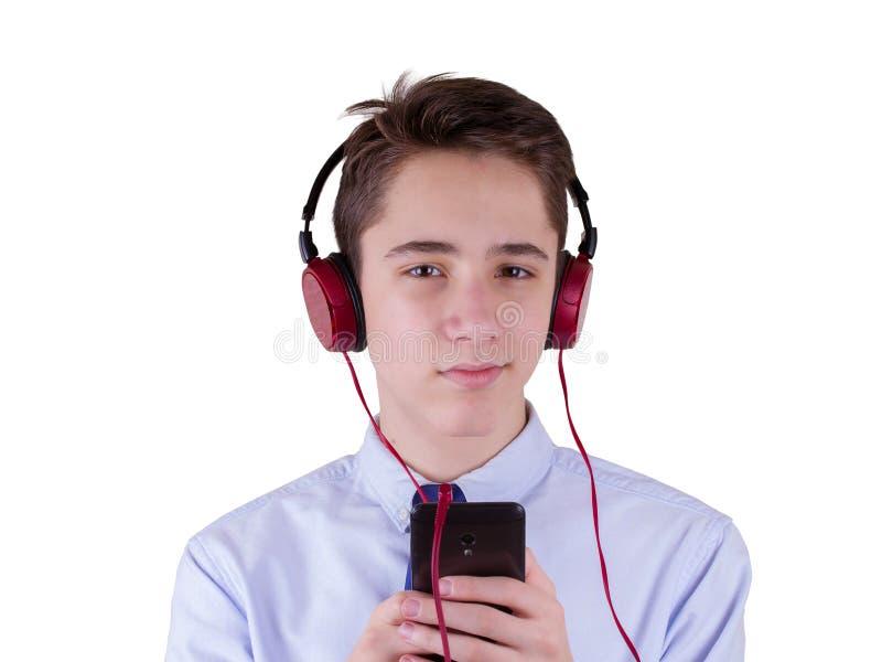 Teenager-tragende Kopfhörer und Hören Musik, telefonisch in Verbindung stehend Getrennt auf weißem Hintergrund lizenzfreie stockfotografie