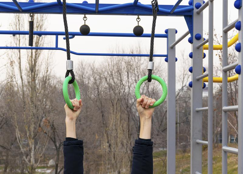 A teenager trains on a sports field on the street on sports rings. Hands hold on sport rings. stock images