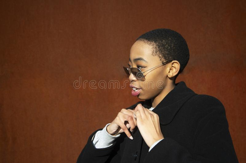 Teenager trendy African woman portrait with black coat and sunglasses on red orange rust metal background royalty free stock photos