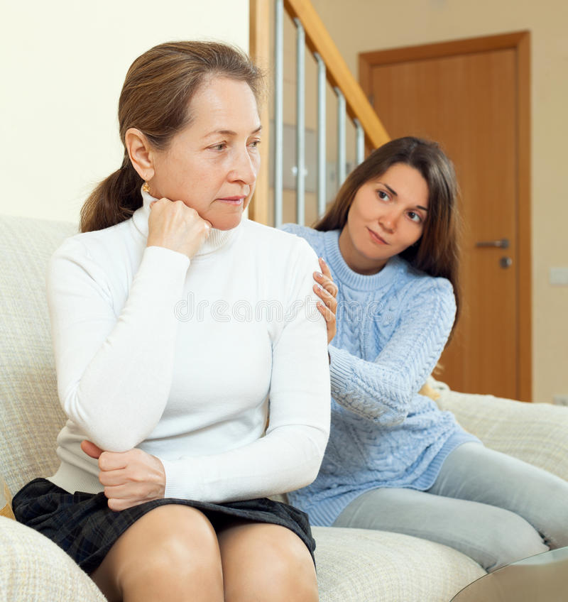 Teenager tries reconcile with her mother after conflict. Focus on mature woman stock image