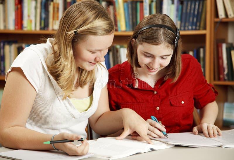 Teenager tut Heimarbeit in der Bibliothek stockfotos