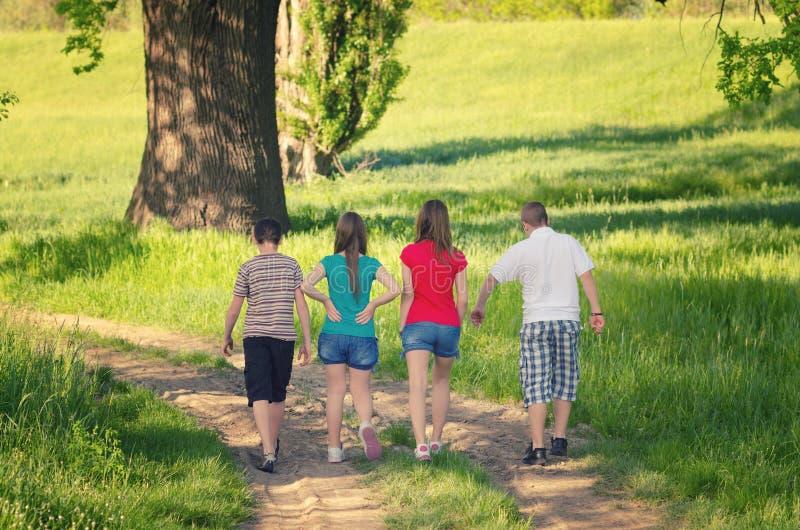 Teenager und Mädchen, die in Natur am sonnigen Frühlingstag gehen lizenzfreie stockbilder