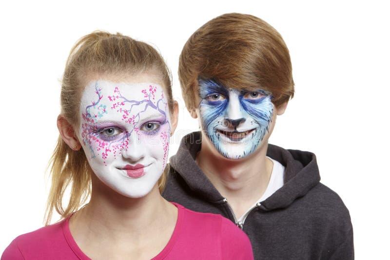 Teenager und Mädchen mit Gesichtsmalerei-Geishamädchen und -wolf stockbilder