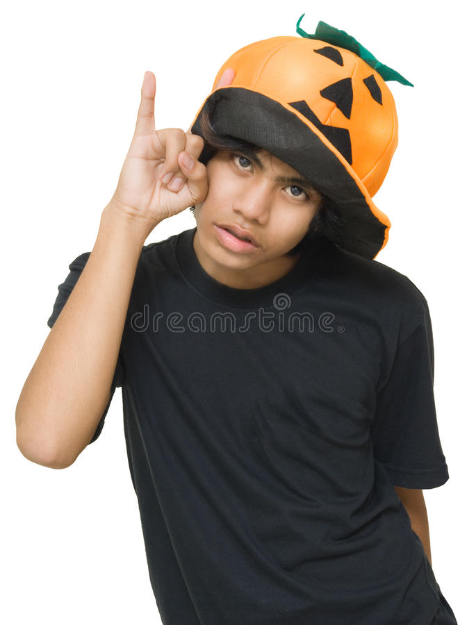 Teenager w pumpkin hat. Indian male teenager with Halloween pumpkin hat pointing up with finger as if warning with a dejected facial expression. Isolated over royalty free stock photos