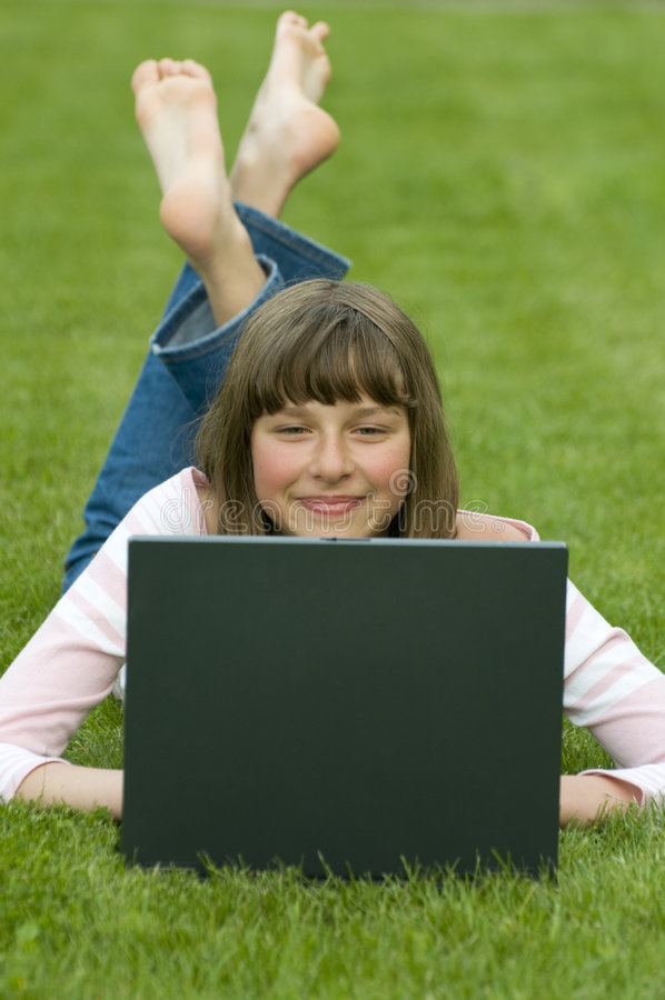 Teenager working at computer on the grass royalty free stock image