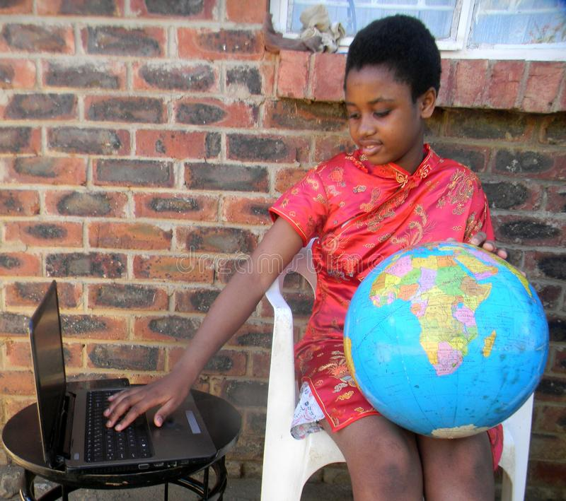 Teenager with a world globe map using laptop computer royalty free stock image